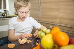Portrait of boy at home peeling a tangarine