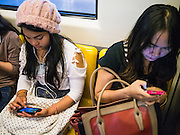 19 APRIL 2013 - BANGKOK, THAILAND:   Women on the BTS Skytrain (Bangkok Mass Transit) in Bangkok use their smart phones during their commute. The system consists of 32 stations along two lines: the Sukhumvit Line running northwards and eastwards, terminating at Mo Chit and Bearing respectively, and the Silom Line which plies Silom and Sathon Roads, the Central Business District of Bangkok, terminating at the National Stadium and Wongwian Yai. The lines interchange at Siam Station and have a combined route distance of 55 km.     PHOTO BY JACK KURTZ