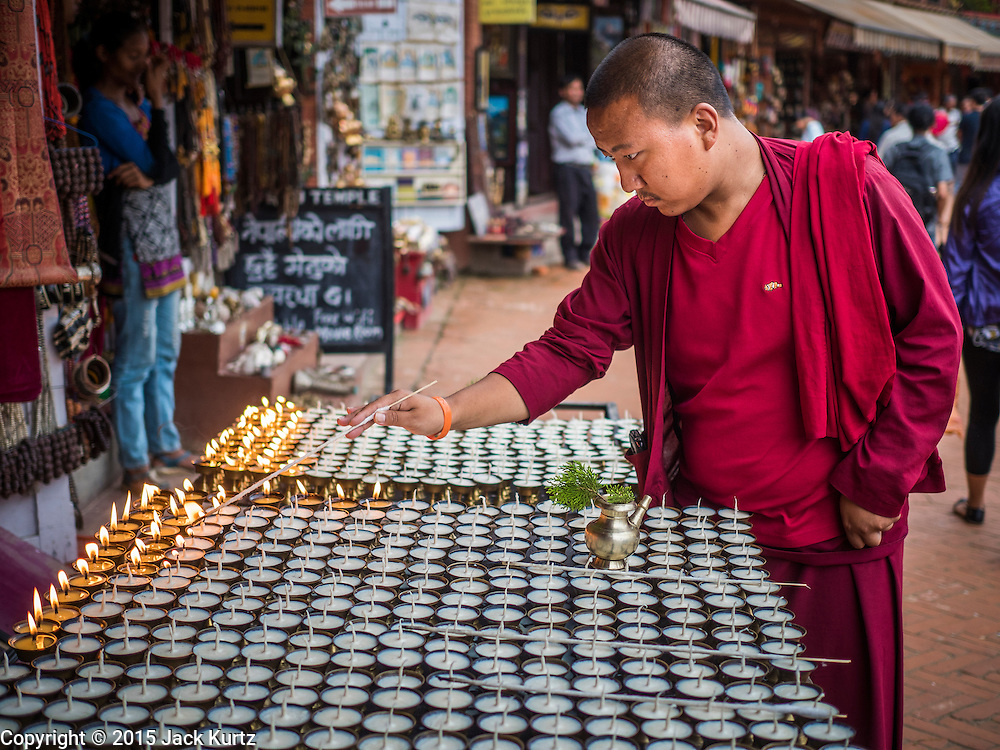 31 JULY 2015 - KATHMANDU, NEPAL: A Tibetan Buddhist monk prays over butter lamps during the full moon processions at Bodhnath Stupa. Bodhnath Stupa in the Bouda section of Kathmandu is one of the most revered and oldest Buddhist stupas in Nepal. The area has emerged as the center of the Tibetan refugee community in Kathmandu. On full moon nights thousands of Nepali and Tibetan Buddhists come to the stupa and participate in processions around the stupa. The stupa was heavily damaged in the earthquake of 25 April 2015 and people are no longer allowed to climb on the stupa, now they walk around the base and pray with butter lamps.   PHOTO BY JACK KURTZ