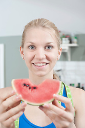 Young woman eating slice of watermelon in the kitchen and smiling, Bavaria, Germany