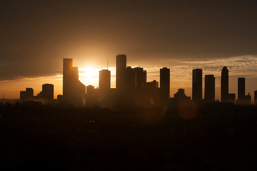 Sun setting behind the silhouetted downtown Houston skyline.