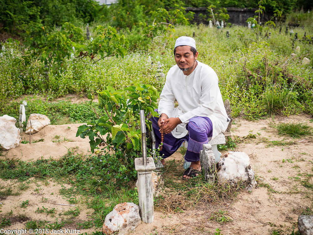 19 JUNE 2015 - PATTANI, PATTANI, THAILAND:  A man prays next to a grave of his father in the Muslim cemetery in Pattani. Perkuboran To'Ayah is the Muslim cemetery in Pattani. It is more than 150 years old. The last Sultan of Pattani, who ruled until Siam (Thailand) annexed Pattani is buried in the cemetery. Many victims of political and sectarian violence that has wracked Thailand's three Muslim majority provinces, Pattani, Narathiwat and Yala are also buried in the cemetery. On Fridays, after morning prayers, Muslim men come to the cemetery to tend to the graves of their family members.  PHOTO BY JACK KURTZ