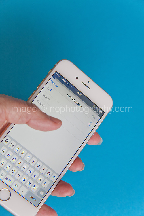 Sending an email on a Gold and white Apple iPhone 6 against a blue background