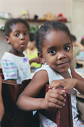 Nursery school children sitting at table in classroom,