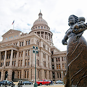 "In the foreground is a statue in the grounds of the Texas State Capitol in Austin titled ""Texas Pioneering Woman"" honoring the prioneer women of early Texas. It was presented to the state by the Daughters of the Republic of Texas, District VIII, in 1998. In the background is the Texas State Capitol building."