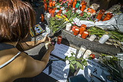 August 18, 2017 - Barcelona, Catalonia, Spain - A mourner places a candle at a makeshift memorial at Canaletas Fountains in Las Ramblas where a van ploughed through the crowds during a 550 meter long jihadist terror trip. Thirteen people were killed and almost 80 wounded, 15 seriously, when the van tore through the crowd. (Credit Image: © Matthias Oesterle via ZUMA Wire)