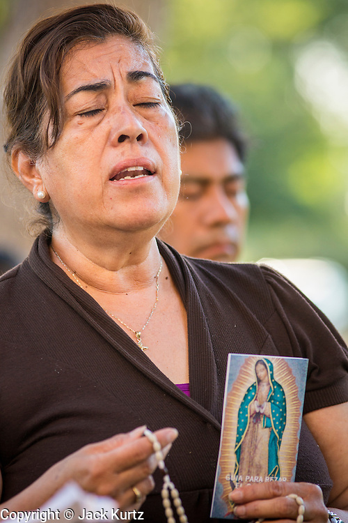 18 JUNE 2012 - PHOENIX, AZ: A woman prays during a vigil against SB 1070 Monday. About 20 people, members of the immigrant rights' group Promise AZ (PAZ) held a prayer vigil at the Arizona State Capitol in Phoenix Monday praying that the US Supreme Court would overturn SB 1070, Arizona's controversial anti-immigrant law. The court's ruling had been expected Monday, June 18 but the the court said the ruling would not come out until later this month. Members of PAZ said they would continue their vigil until the ruling was issued.     PHOTO BY JACK KURTZ