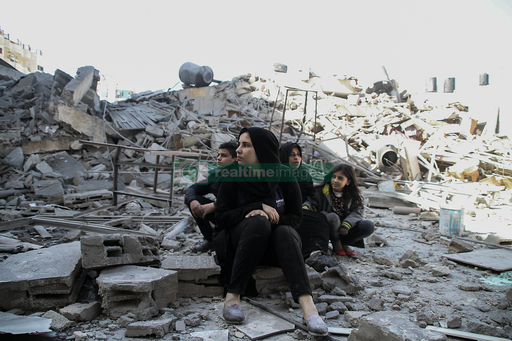 March 26, 2019 - Gaza - Palestinians look at the rubble of what was their homes before the Israeli bombardments of the previous day. Israeli warplanes carried out dozens of airstrikes across the southern, central, and northern Gaza Strip after a Gaza rocket struck an Israeli house north of Tel Aviv, in central Israel, injuring seven Israelis. Israeli warplanes targeted Hamas sites, as well as dozens of residential and commercial buildings, and according to the Palestinian Ministry of Health in Gaza, seven Palestinians suffered various injuries due to the airstrikes (Credit Image: © Ahmad Hasaballah/IMAGESLIVE via ZUMA Wire)