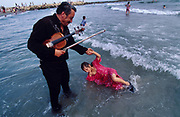 Europe, France, Camargue, Saintes Maries de la Mer, Gypsy Pilgrimmage 'Pelerinage des Gitans aux Saintes Maries de la Mer'. Manouche with his violin and his daughter in the surf at the end of Sara's procession. Gypsies from all over the world come to celebrate their patron Saint Sara who is carried by them from the church to the sea-shore. May 24th and 25th every year.