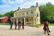 """Old Bethpage, New York, USA. 30th August, 2015. A 19th Century gentleman wearing a top hat, and American Civil War soldiers from the 14th Brooklyn Regiment (14th New York State Militia) AKA The Brooklyn Chasseurs, are portrayed in front of the yellow Noon Inn tavern during the Old Time Music Weekend at the Old Bethpage Village Restoration. During their historical reenactments, members of the non-profit 14th Brooklyn Company E wear reproductions of """"The """"Red Legged Devils"""" original Union army uniform."""