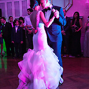 Bride and Groom dance together in low key purple spotlight