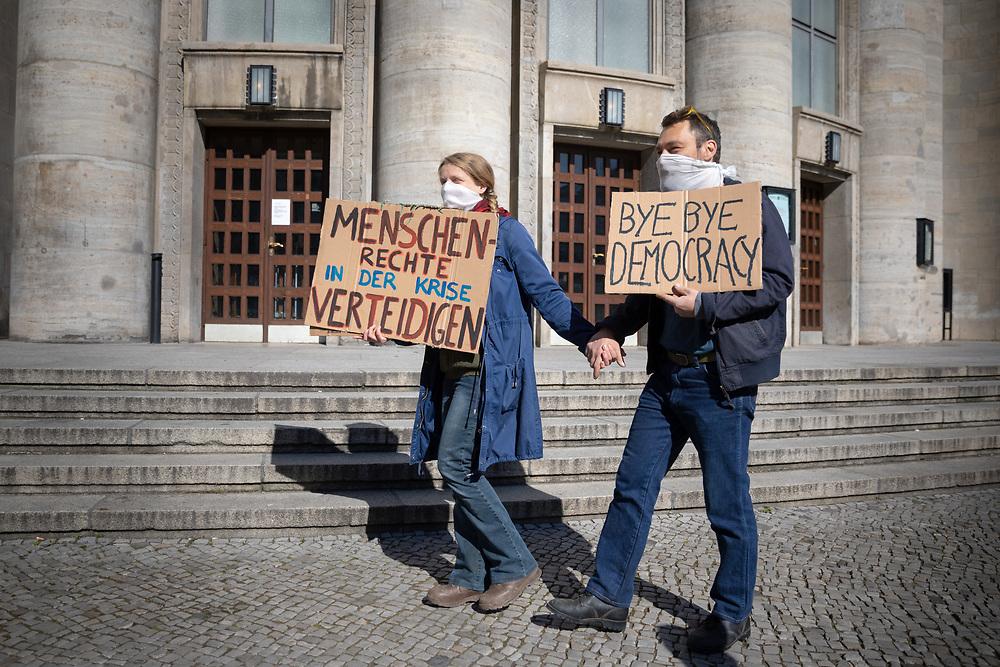 """Trotz der Verordnung mit Ausgansbeschränkung, Demonstrationsverbot und Kontaktverbot zur Eindämmung der COVID-19 - Pandemie (Coronavirus SARS-CoV-2) protestieren über 100  Menschen, darunter viele Verschwörungstheoretiker auf der """"Hygienedemo für Verfassung, Grundrechte & transparente Gestaltung der neuen Wirtschaftsregeln"""" organisiert von der """"Kommunikationsstelle Demokratischer Widerstand Berlin"""" gegen die Einschränkung von Grundrechte im Rahmen der Eindämmungsverordnung des Infektionsschutzgesetzes. Die Demonstranten kritisieren die Einschränkung der Versammlungsfreiheit, relativieren aber auch die Gefährlichkeit des Virus. Polizisten lösen die Versammlung auf, und stellen von einigen Demonstranten die Personalien fest. Demonstranten mit Schildern: """"Menschenrechte in der Krise verteidigen"""" und """"Bye Bye Democracy"""" <br /> <br /> [© Christian Mang - Veroeffentlichung nur gg. Honorar (zzgl. MwSt.), Urhebervermerk und Beleg. Nur für redaktionelle Nutzung - Publication only with licence fee payment, copyright notice and voucher copy. For editorial use only - No model release. No property release. Kontakt: mail@christianmang.com.]"""