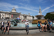 Summertime in London, England, UK. Tourists sitting in the summer sunshine beside the fountains in Trafalgar Square. This area is a large public space and tourist attraction right at the heart of the West End.