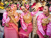 """14 JANUARY 2015 - BANGKOK, THAILAND: Girls in traditional attire pose for a """"selfie"""" before the 2015 Discover Thainess parade. The Tourism Authority of Thailand (TAT) sponsored the opening ceremony of the """"2015 Discover Thainess"""" Campaign with a 3.5-kilometre parade through central Bangkok. The parade featured cultural shows from several parts of Thailand. Part of the """"2015 Discover Thainess"""" campaign is a showcase of Thailand's culture and natural heritage and is divided into five categories that match the major regions of Thailand – Central Region, North, Northeast, East and South.     PHOTO BY JACK KURTZ"""