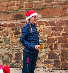 Pictured: Santa Beach Run on the scenic East Lothian coast. This new event is aimed at athletes, casual runners and families. It is hosted by Project Trust with proceeds enabling local school leavers to spend a year volunteering in India/Honduras to teach at a school with few teaching materials. The fastest gril with her medal. 15 December 2018  <br /> <br /> Sally Anderson | EdinburghElitemedia.co.uk
