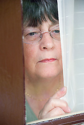 Woman; looking scared; staring through curtains,