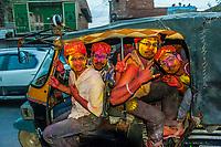 Men riding an auto rickshaw leaving the Lathmar Holi (Holi, Festival of Colors), Barsana, near Mathura, Uttar Pradesh, India.