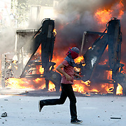 A protestor stands in front of burning excavator vehicle during a clash with Turkish riot police at Taksim Square in Istanbul, Turkey, 11 June 2013. Photo by AYKUT AKICI/TURKPIX