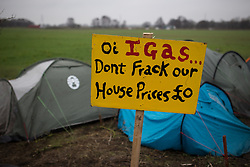 """© Licensed to London News Pictures . 24/01/2014 . Barton Moss Road , Manchester , UK . Sign reading """" Oi IGAS...don't frack our house prices £0 """" in front of tents pitched at the protest site . Site of a protest camp on Barton Moss Road where anti-fracking demonstrators are based on an access road leading to an iGas fracking site as today (24th January 2014) Greater Manchester Police announce two further arrests from the ongoing protest after reporting that a security guard was threatened and assaulted on Barton Moss Road on Monday (20th January 2014) . Photo credit : Joel Goodman/LNP"""