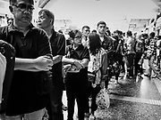 """11 APRIL 2017 - BANGKOK, THAILAND:  Travelers wait in line at the ticket counter in the main waiting room in Hua Lamphong train station during the Songkran travel period at Hua Lamphong train station in Bangkok. Songkran is the traditional Thai Lunar New Year. It is celebrated, under different names, in Thailand, Myanmar, Laos, Cambodia and some parts of Vietnam and China. In most places the holiday is marked by water throwing and water fights and it is sometimes called the """"water festival."""" This year's Songkran celebration in Thailand will be more subdued than usual because Thais are still mourning the October 2016 death of their revered Late King, Bhumibol Adulyadej. Songkran is officially a three day holiday, April 13-15, but is frequently celebrated for a full week. Thais start traveling back to their home provinces over the weekend; busses and trains going out of town have been packed.    PHOTO BY JACK KURTZ"""