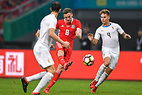 """Andy King, center, of Wales national football team kicks the ball to make a pass against players of Uruguay national football team in their final match during the 2018 Gree China Cup International Football Championship in Nanning city, south China's Guangxi Zhuang Autonomous Region, 26 March 2018.<br /> <br /> Edinson Cavani's goal in the second half helped Uruguay beat Wales to claim the title of the second edition of China Cup International Football Championship here on Monday (26 March 2018). """"It was a tough match. I'm very satisfied with the result and I think that we can even get better if we didn't suffer from jet lag or injuries. I think the result was very satisfactory,"""" said Uruguay coach Oscar Tabarez. Wales were buoyed by a 6-0 victory over China while Uruguay were fresh from a 2-0 win over the Czech Republic. Uruguay almost took a dream start just 3 minutes into the game as Luis Suarez's shot on Nahitan Nandez cross smacked the upright. Uruguay were dealt a blow on 8 minutes when Jose Gimenez was injured in a challenge and was replaced by Sebastian Coates. Inter Milan's midfielder Matias Vecino of Uruguay also fired at the edge of box from a looped pass but only saw his attempt whistle past the post. Suarez squandered a golden opportunity on 32 minutes when Ashley Williams's wayward backpass sent him clear, but the Barca hitman rattled the woodwork again with goalkeeper Wayne Hennessey well beaten."""