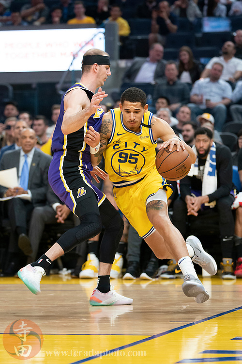 February 27, 2020; San Francisco, California, USA; Golden State Warriors forward Juan Toscano-Anderson (95) dribbles the basketball against Los Angeles Lakers guard Alex Caruso (4) during the fourth quarter at Chase Center.