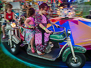 26 JUNE 2019 - CENTRAL CITY, IOWA: Children ride a Merry-Go-Round on the midway at the Linn County Fair. Summer is county fair season in Iowa. Most of Iowa's 99 counties host their county fairs before the Iowa State Fair, August 8-18 this year. The Linn County Fair runs June 26 - 30. The first county fair in Linn County was in 1855. The fair provides opportunities for 4-H members, FFA members and the youth of Linn County to showcase their accomplishments and talents and provide activities, entertainment and learning opportunities to the diverse citizens of Linn County and guests.      PHOTO BY JACK KURTZ