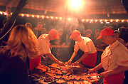 Cooks age 24 flipping meat on grill at outdoor barbecue restaurant.  Krakow Poland