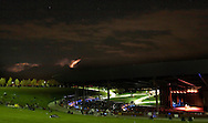 Lightning strikes in the distance at left as Arlo Guthrie plays at Bethel Woods Center for the Arts on Aug. 17, 2007.