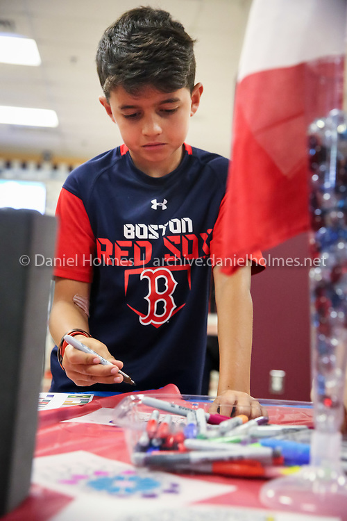 (6/14/16, UPTON, MA) Third-grader Jacob Nagda colors a stained glass window at the France table during International Night at Nipmuc High School in Upton on Tuesday. Daily News and Wicked Local Photo/Dan Holmes