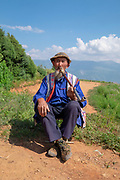 Local mature man smoking a pipe at a small village in the mountains near Kumming, Yunnan province in southwest China in September