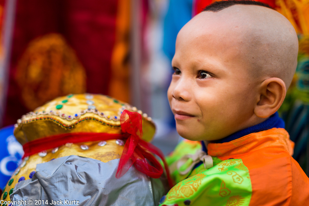 24 SEPTEMBER 2014 - BANGKOK, THAILAND: A boy waits to march in the Vegetarian Festival Parade in Bangkok. He was dressed as a Taoist God. The Vegetarian Festival is celebrated throughout Thailand. It is the Thai version of the The Nine Emperor Gods Festival, a nine-day Taoist celebration beginning on the eve of 9th lunar month of the Chinese calendar. During a period of nine days, those who are participating in the festival dress all in white and abstain from eating meat, poultry, seafood, and dairy products. Vendors and proprietors of restaurants indicate that vegetarian food is for sale by putting a yellow flag out with Thai characters for meatless written on it in red.    PHOTO BY JACK KURTZ