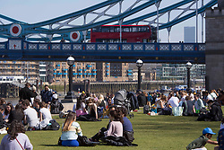 © Licensed to London News Pictures. 04/04/2021. London, UK. Members of the public relax in the sun on Easter Sunday in Tower Bridge, central London. Photo credit: Marcin Nowak/LNP