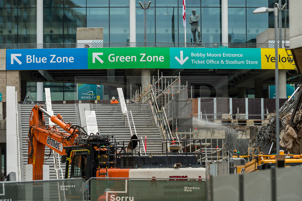 © Licensed to London News Pictures. 21/11/2020. LONDON, UK.  The statue of England's 1966 World Cup winning side, Bobby Moore, looks down at the work to demolish the iconic ramps on Wembley Way that lead up to Wembley Stadium. The ramps, known as pedways, have been used for 46 years by fans attending football matches and other events at the stadium. A new set of steps (partially constructed, seen lower left) will replace them and be in place for 2021 at a cost of £18m.  Photo credit: Stephen Chung/LNP
