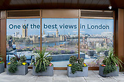 A banner that shows a premium rooftop property view of the Houses of Parliament is seen outside the offices of a city estate agent, on 24th February 2021, in London, England.