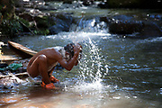 Young Guarani male naked having a wash in a natural pool in the woods. The Guarani are one of the most populous indigenous populations in Brazil, but with the least amount of land. They mostly live in the State of Mato Grosso do Sul and Mato Grosso. Their tradtional way of life and ancestral land is increasingly at risk from large scale agribusiness and agriculture. There have been recorded cases and allegations of violence between owners of large farms and the Guarani communities in this region.