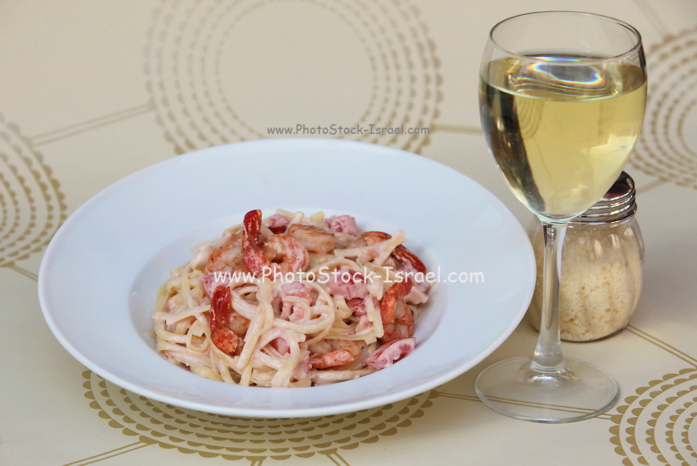 plate of linguine with shrimps and glass of white wine