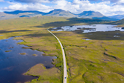 Aerial view of A82 road crossing Rannoch Moor in summer with Loch Ba on the left , Scotland, UK