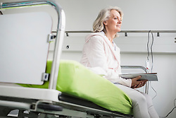 Patient in hospital sitting on bed