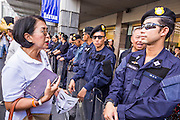 """09 JUNE 2013 - BANGKOK, THAILAND: A Thai woman who is a member of the White Masks, confronts Thai riot police during a protest against the government of Yingluck Shinawatra at Central World. The White Mask protesters wear the Guy Fawkes mask popularized by the movie """"V for Vendetta"""" and the protest groups Anonymous and Occupy. Several hundred members of the White Mask movement gathered on the plaza in front of Central World, a large shopping complex at the Ratchaprasong Intersection in Bangkok, to protest against the government of Thai Prime Minister Yingluck Shinawatra. They say that her government is corrupt and is a """"puppet"""" of ousted (and exiled) former PM Thaksin Shinawatra. Thaksin is Yingluck's brother. She was elected in 2011 when her brother endorsed her.     PHOTO BY JACK KURTZ"""