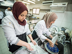 25 February 2020, Jerusalem: Students Sama'a Siam (right( and Hayat Mhesl (left) do the dishes as they finish catering class at the vocational training centre in Beit Hanina. The Lutheran World Federation's vocational training centre in Beit Hanina offers vocational training for Palestinian youth across a range of different professions, providing them with the tools needed to improve their chances of finding work.