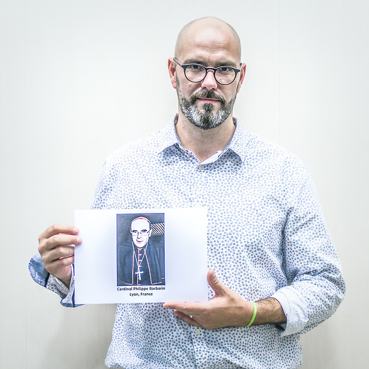 """2018<br /> Francois Devaux, a survivor and an activist from France, poses for a portrait showing a picture of the Cardinal Philippe Barbarin who was contacted by a victim of Rev. Bernard Preynat, a priest whose crimes had been known to the Lyon archdiocese since at least 1991, the cardinal sent Preynat's case to the Congregation for the Doctrine of the Faith, receiving a reply in February 2015 from Archbishop Luis Francisco Ladaria Ferrer, S.J., secretary to the CDF Prefect, Ladaria Ferrer's reply read in part: """"The Congregation, having carefully studied the cases of the priest of your diocese, Bernard Preynat"""" recommends """"prescribing the measures disciplinary measures, while avoiding the public scandal.""""  © Simone Padovani"""