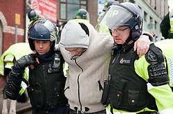 © under license to London News Pictures.  05/02/2011. Police medics lead an injured English Defence League member away after he fell off the top of a brick wall onto concrete at a protest in Luton. Photo credit should read Michael Graae/London News Pictures