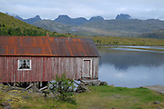 A red-painted Rorbu fisherman's cabin on 25th August 2016 in Lofoten, Norway. The Lofoten islands are famous for their jagged mountains, red-painted rorbu cabins and racks with fish hanging closely packed to dry.