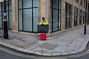A man in a lime green jumper and with red trolley baggage, uses his mobile phone on a street corner in central London, on 5th January 2019, in London, England.