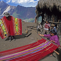 A horseman tries on a serape woven by a homesteader at her family's homestead in Peru's Cordillera Vilcabamba.