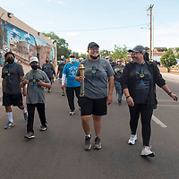 Special Olympics athlete Shelby Peterson, center, leads the Law Enforcement Torch Run as she carries the torch on Second Street accompanied by Judith Goins, right, Saturday morning in Gallup.