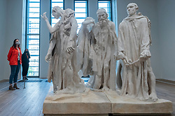 """© Licensed to London News Pictures. 11/05/2021. LONDON, UK. Staff members pose with the original plaster cast of """"The Burghers of Calais"""", 1889, by Auguste Rodin. Preview at Tate Modern of """"The Making of Rodin"""", a major new exhibition of over 200 sculpture works by Auguste Rodin, many of which have never been shown outside France. The exhibition marks the reopening of the museum as the UK government eases certain coronavirus lockdown restrictions and is open 18 May to 21 November.  Photo credit: Stephen Chung/LNP"""