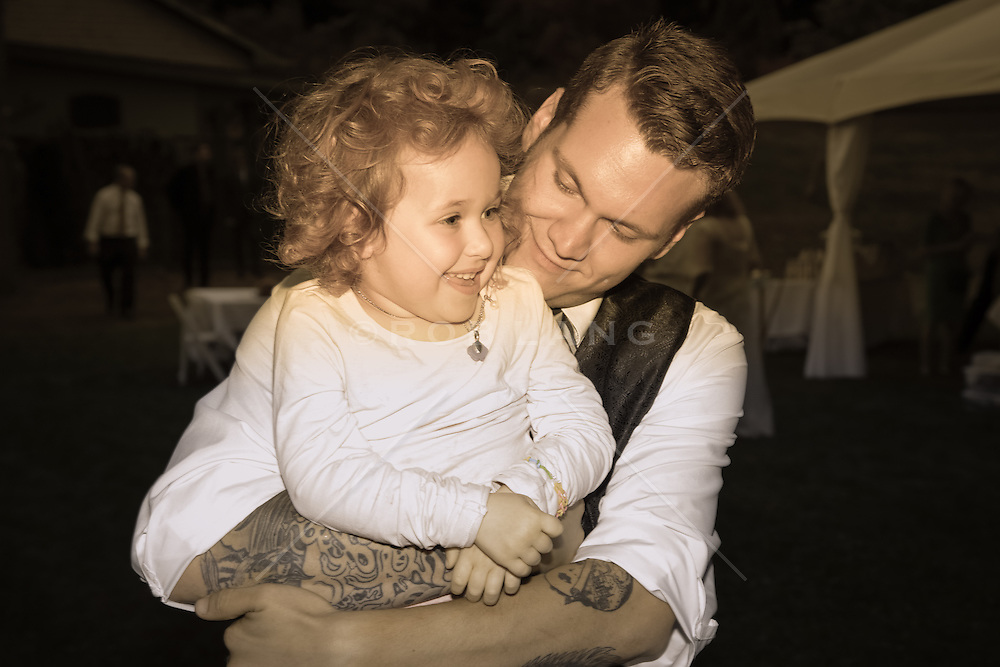 young man with tattoos holding a little girl