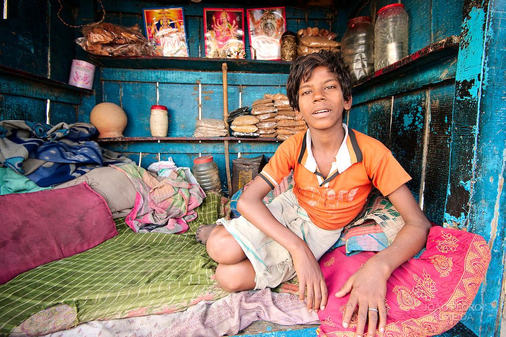 Young boy sitting at a small stand at Harishchandra ghat selling spices for cremation